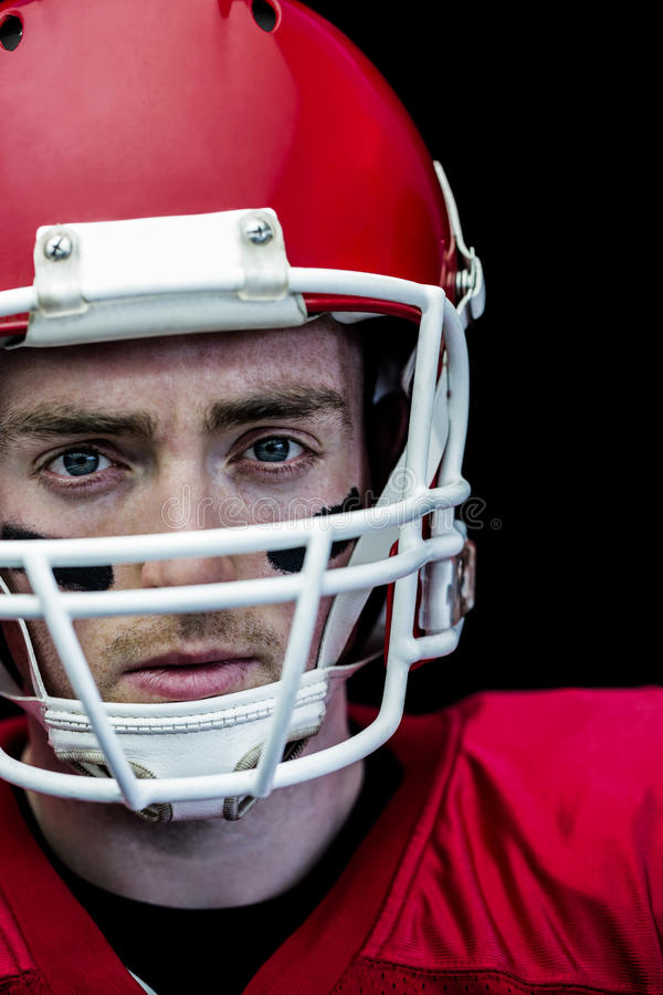 Portret van geconcentreerde Amerikaanse voetbalster die zijn helm dragen royalty-vrije stock afbeeldingen