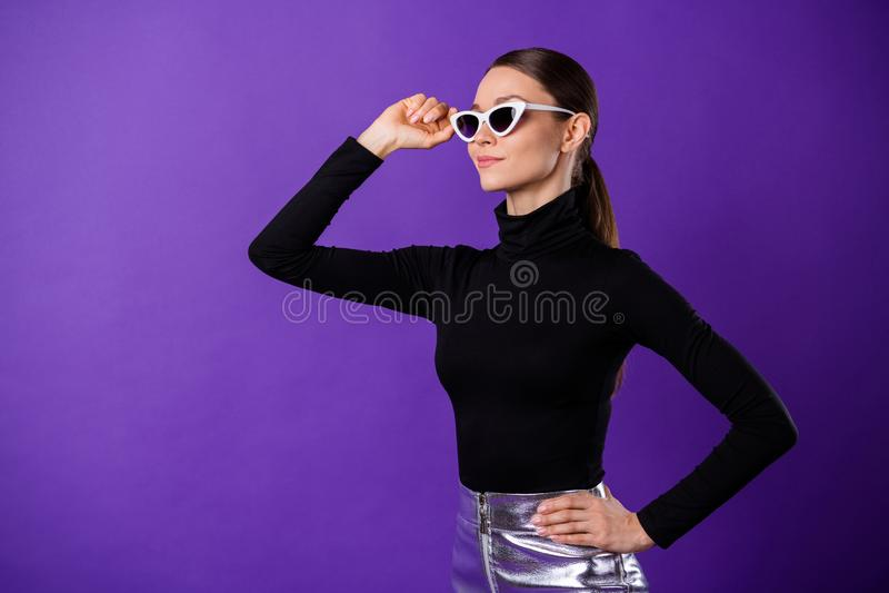 Portret van geconcentreerde zoete persoon die wat betreft haar bril zwarte col dragen die over purpere violette achtergrond wordt stock foto