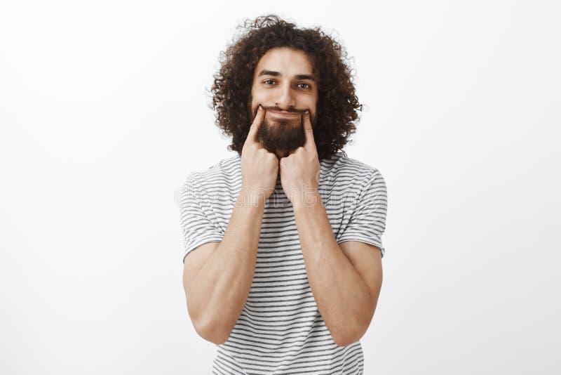 Portret van gedeprimeerde ongelukkige knappe Spaanse gebaarde kerel met krullend haar, die glimlach met wijsvingers trekken, het  royalty-vrije stock afbeeldingen