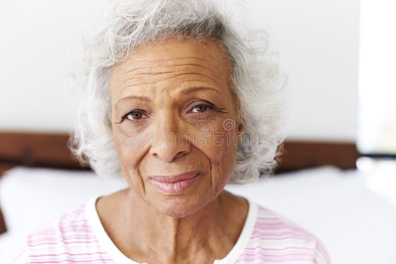 Portret van Gedeprimeerde Vrouw het Kijken Ongelukkige Zitting aan Kant van Bed thuis royalty-vrije stock afbeelding