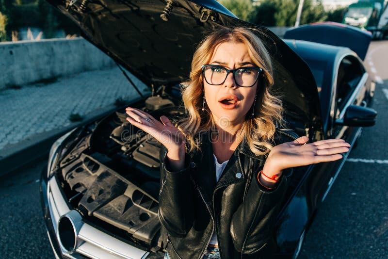 Portret van gefrustreerde jonge vrouw met krullende haar dichtbij gebroken auto met open kap stock foto's