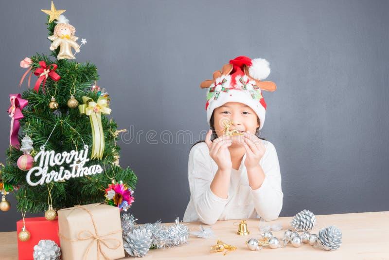 Portret van gelukkig Aziatisch meisje die weinig Kerstboom verfraaien stock fotografie