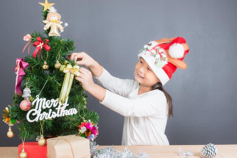 Portret van gelukkig Aziatisch meisje die weinig Kerstboom verfraaien royalty-vrije stock foto's