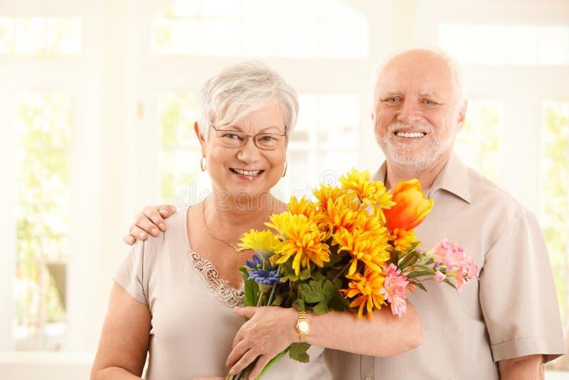 Portret van gelukkig bejaard paar met bloemen stock afbeeldingen