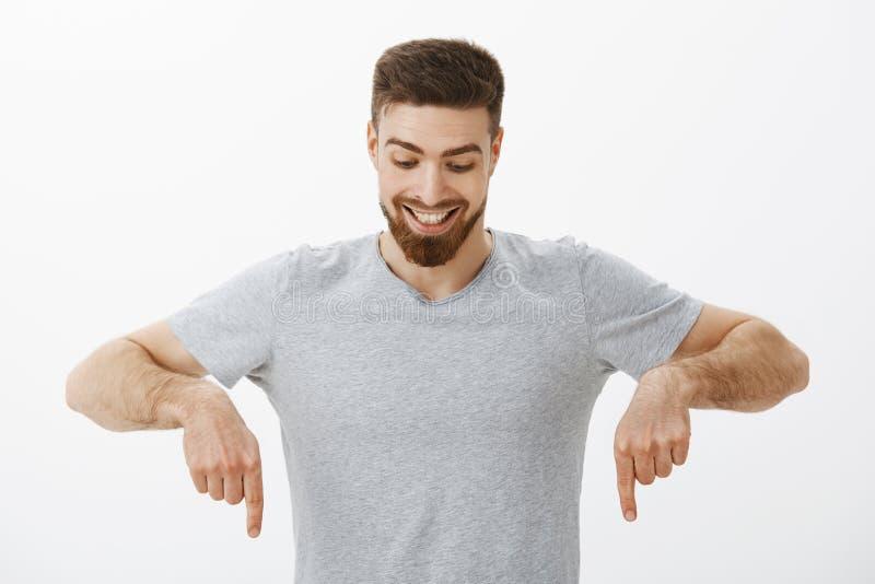 Portret van gelukkig en verbaasd knap mannelijk mannetje met perfect kapsel en baard die en neer kijken richten met royalty-vrije stock foto's