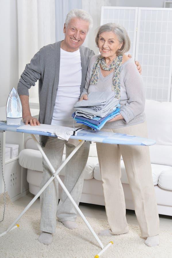 Portret van gelukkig hoger paar tijdens het strijken stock foto