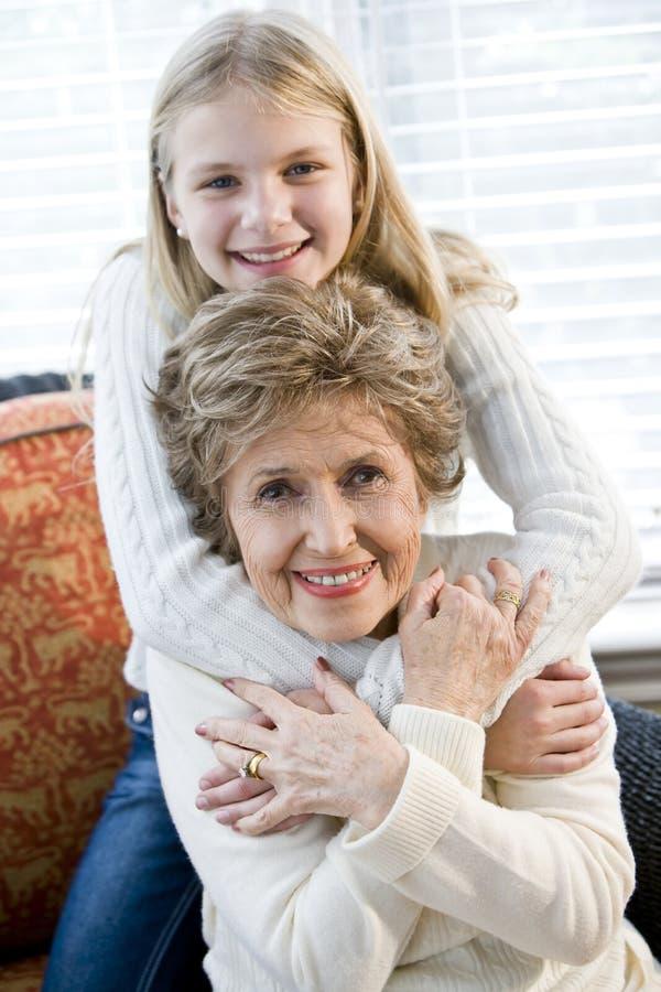 Portret van gelukkig jong meisje dat grootmoeder koestert royalty-vrije stock afbeeldingen