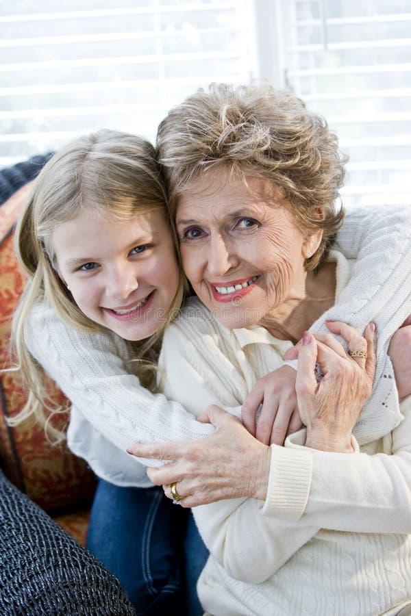 Portret van gelukkig jong meisje dat grootmoeder koestert stock foto's