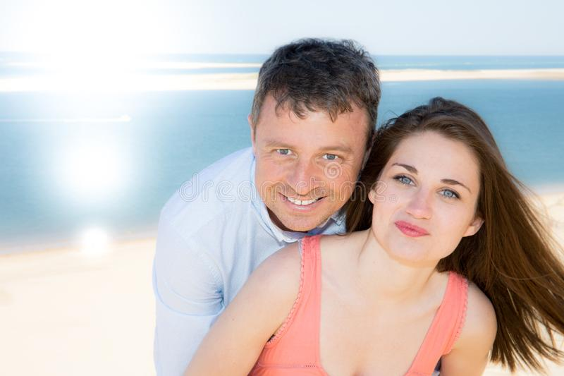 Portret van gelukkig jong paar die van de dag op het strand genieten tijdens vakantie royalty-vrije stock foto