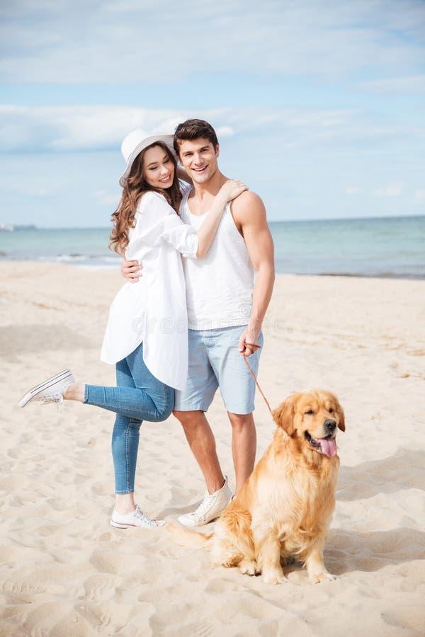Portret van gelukkig jong paar met hond op het strand royalty-vrije stock afbeeldingen