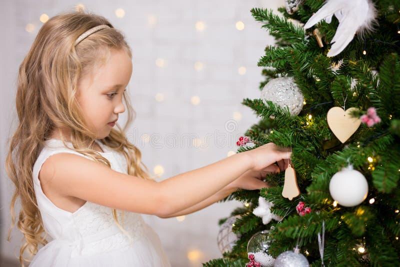 Portret van gelukkig meisje die Kerstboom thuis verfraaien royalty-vrije stock fotografie