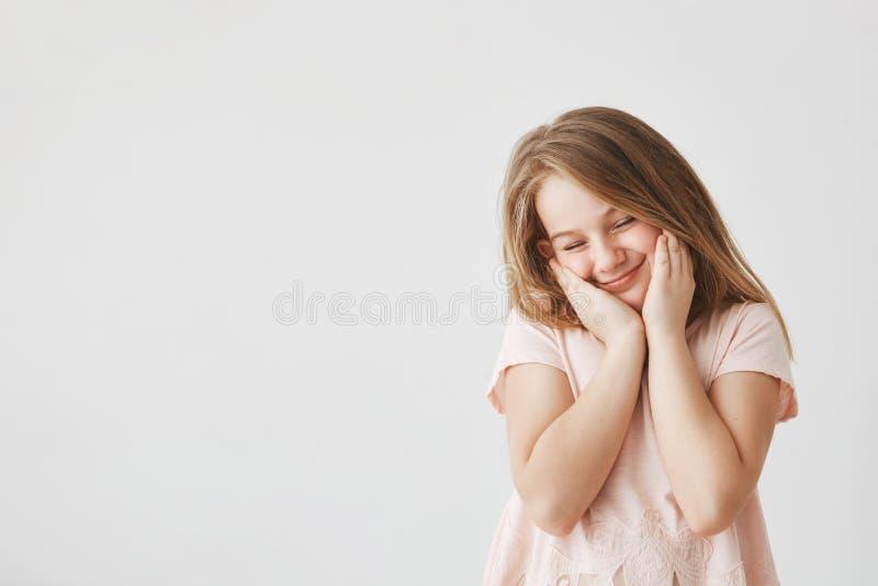Portret van gelukkig mooi meisje die met blond haar in roze t-shirt gezicht met handen drukken, die ogen sluiten, die schuw voele royalty-vrije stock afbeeldingen