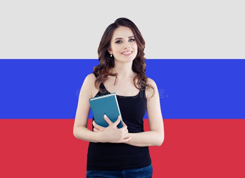 Portret van gelukkig mooi meisje met boek tegen de Russische achtergrond van de Federatievlag De reis en leert Russisch taalconce royalty-vrije stock afbeeldingen