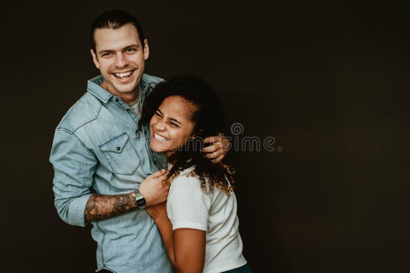Portret van gelukkig opgewekt mengen-ras jong paar in liefde die en pret op de zwarte achtergrond koesteren hebben Verhoudingscon royalty-vrije stock afbeeldingen