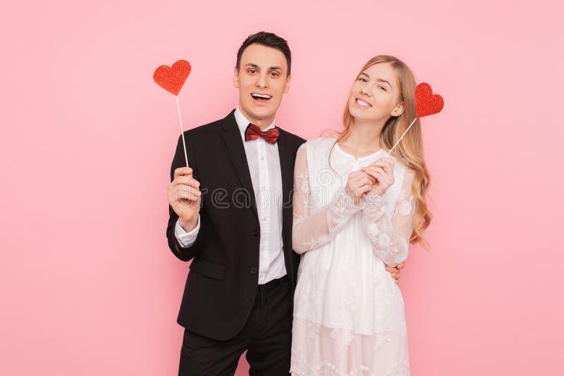 Portret van gelukkig paar in het document van de liefdeholding harten, op roze achtergrond, het concept van de minnaarsdag stock afbeelding