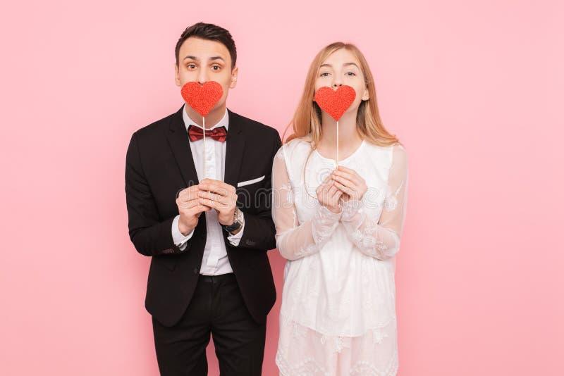 Portret van gelukkig paar in het document van de liefdeholding harten, op roze achtergrond, het concept van de minnaarsdag stock foto's