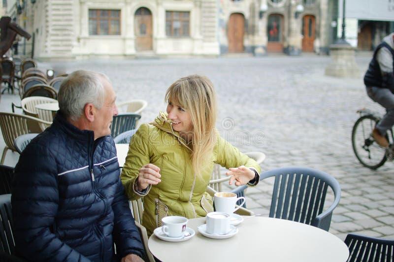 Portret van gelukkig romantisch paar met leeftijdsverschil het drinken koffie in koffie met terras in openlucht in de oude stad stock foto