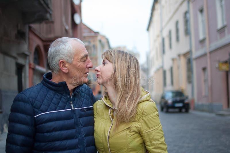 Portret van gelukkig romantisch paar met leeftijdsverschil het kussen in openlucht in de oude stad tijdens de vroege lente of de  royalty-vrije stock afbeelding