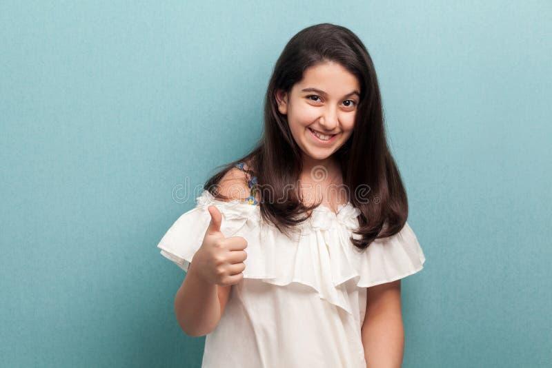Portret van gelukkig tevreden mooi donkerbruin jong meisje met zwart lang recht haar in het witte kledings opstaan, duimen en stock foto