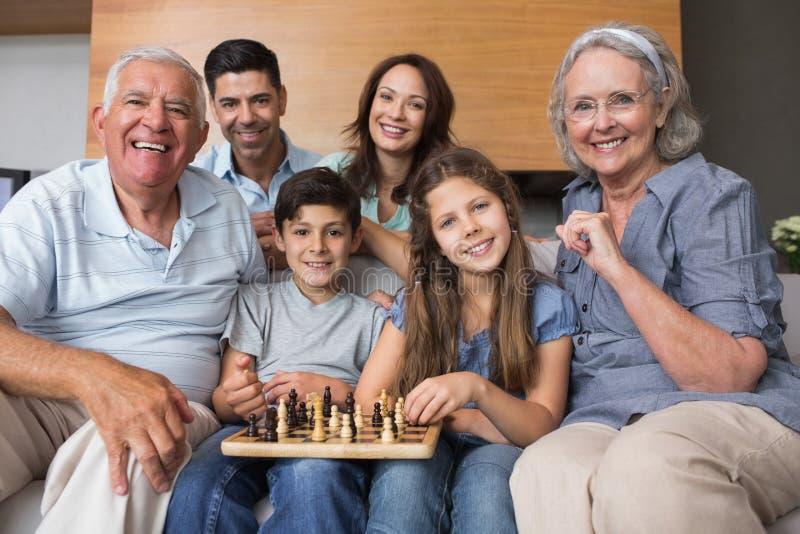 Portret van gelukkig uitgebreid familie het spelen schaak in woonkamer royalty-vrije stock foto