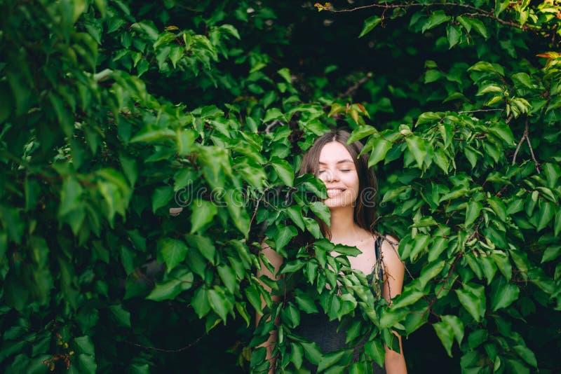 Portret van gelukkig vrij jong tienermeisje die in groene bladeren gezonde natuurlijk glimlachen royalty-vrije stock fotografie
