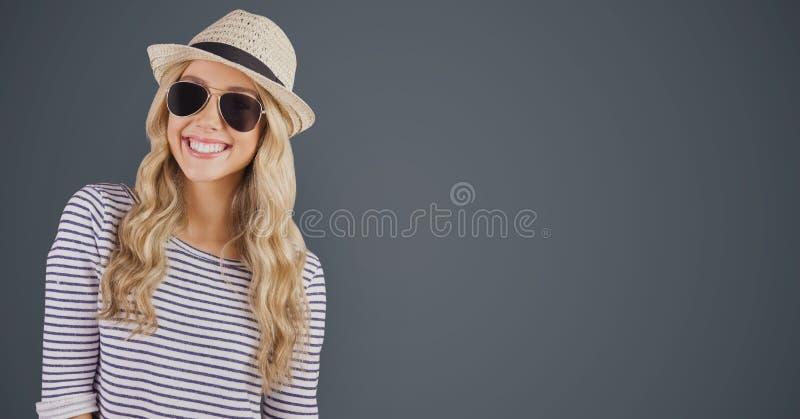 Portret van gelukkig wijfje die hipster zonnebril en zonhoed dragen tegen grijze achtergrond stock afbeeldingen