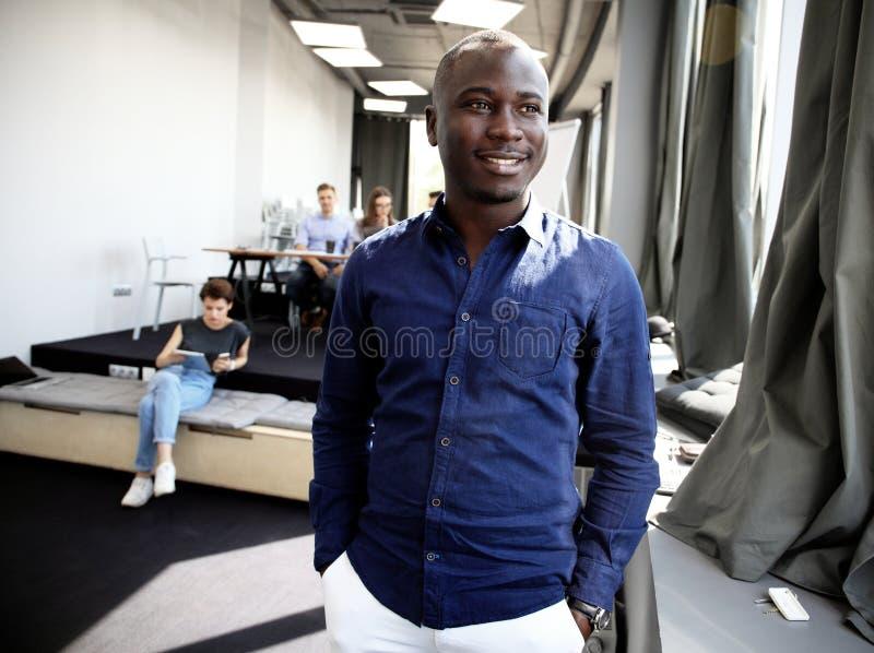 Portret van gelukkige Afrikaanse kerel die camera in werkomgeving bekijken stock fotografie