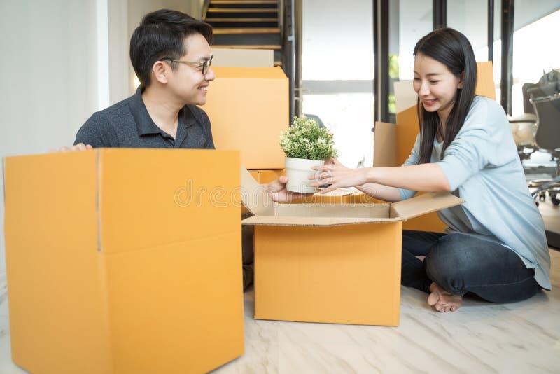 Portret van gelukkige Aziatische familie die zich aan nieuw huis met kartondozen bewegen royalty-vrije stock fotografie