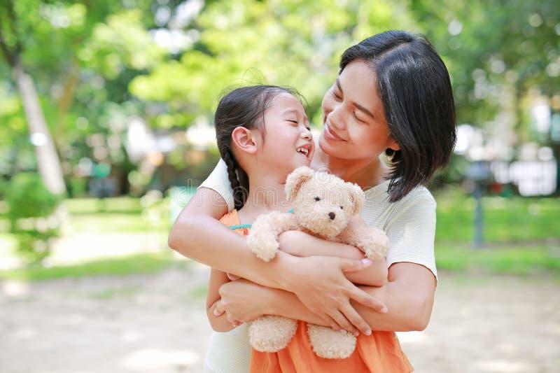 Portret van gelukkige Aziatische moederknuffel dochter en het koesteren van teddybeerpop in de tuin Mamma en kindmeisje met liefd royalty-vrije stock afbeelding