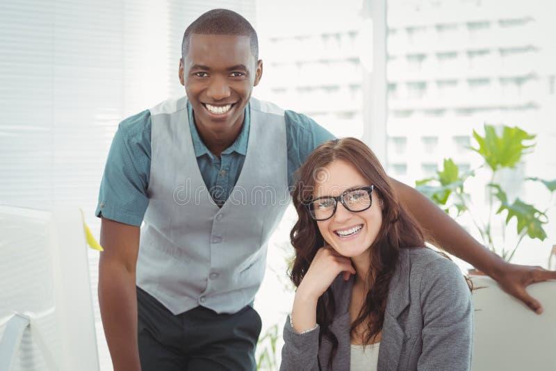 Portret van gelukkige bedrijfsberoeps bij computerbureau stock afbeeldingen