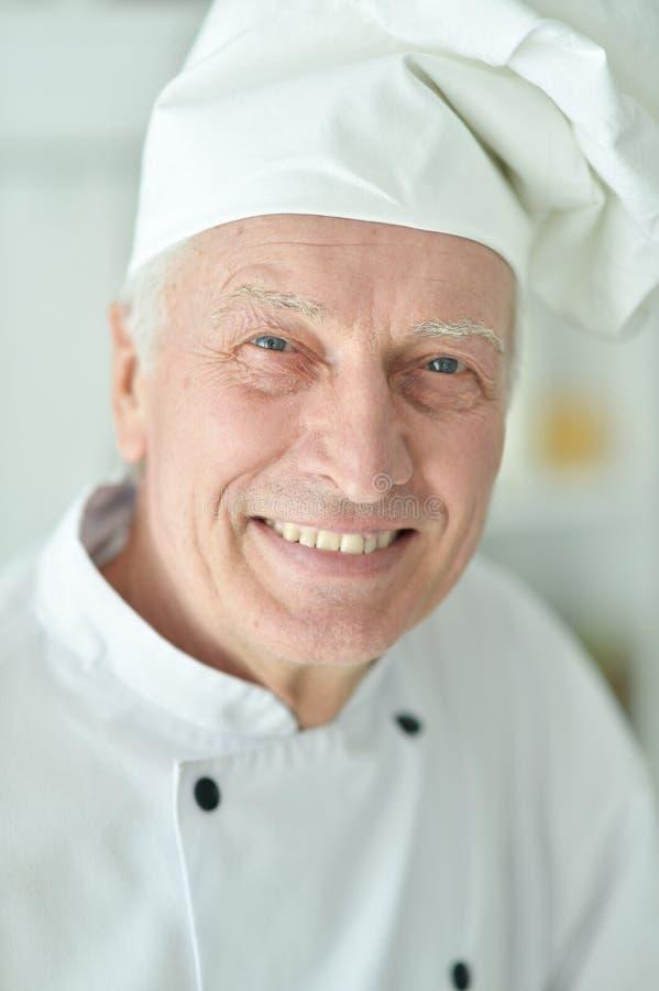Portret van gelukkige bejaarde mannelijke chef-kok die thuis stellen stock afbeelding