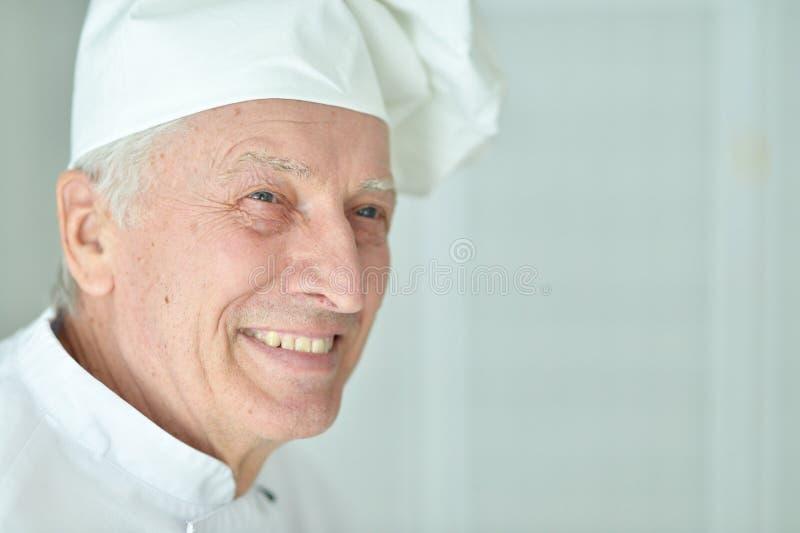 Portret van gelukkige bejaarde mannelijke chef-kok die thuis stellen stock fotografie