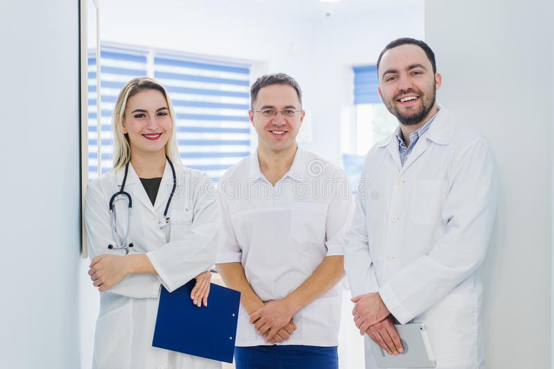 Portret van gelukkige cowerkers met klembord terwijl status bij het ziekenhuis stock afbeelding