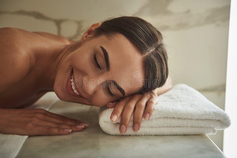 Portret van gelukkige dame die terwijl het liggen op de handdoek glimlachen stock afbeelding