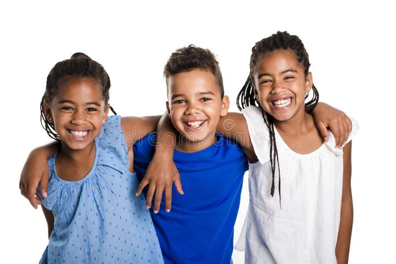 Portret van gelukkige drie zwarte kinderen, witte achtergrond stock foto