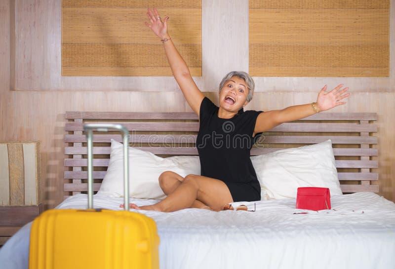 Portret van gelukkige en aantrekkelijke rijpe Aziatische toeristenvrouw die met die grijs haar in de ruimte van het vakantiehotel stock foto
