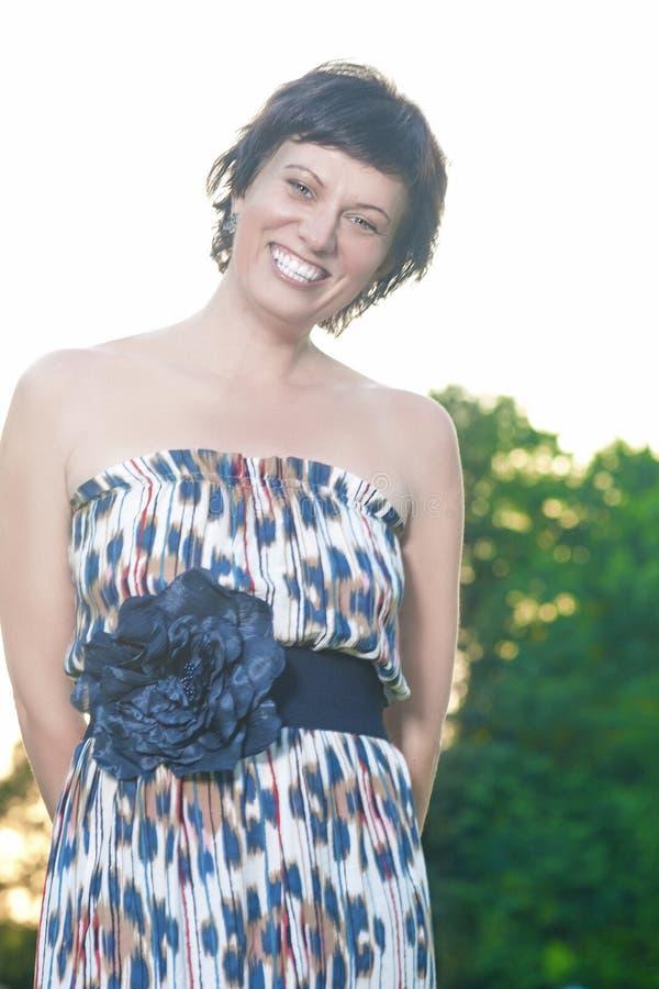 Portret van Gelukkige en het Glimlachen het Kaukasische Donkerbruine Vrouw Stellen in openlucht bij Zonsondergang stock afbeeldingen