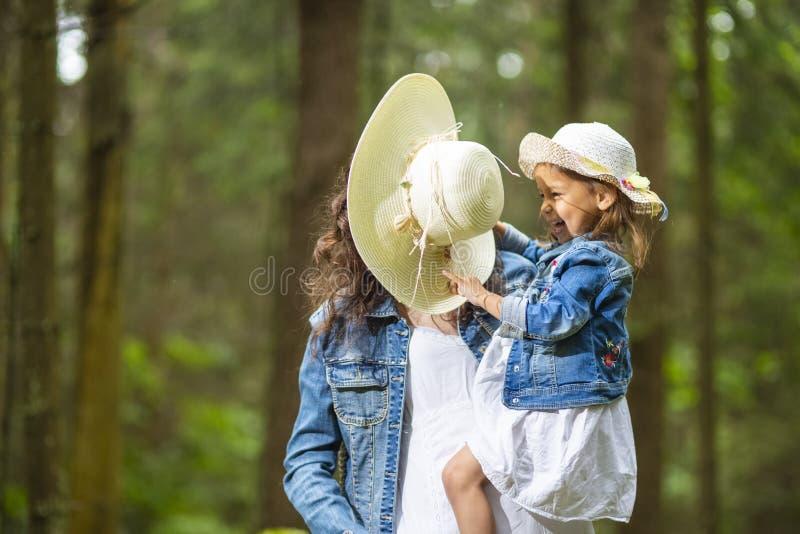 Portret van Gelukkige en Lachende Kaukasische Moeder met haar Weinig Dochter die samen spelen stock fotografie