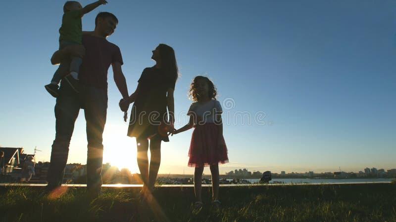 Portret van gelukkige familie bij zonsondergang - vader, moeder, dochter en weinig zoon - silhouet stock afbeeldingen