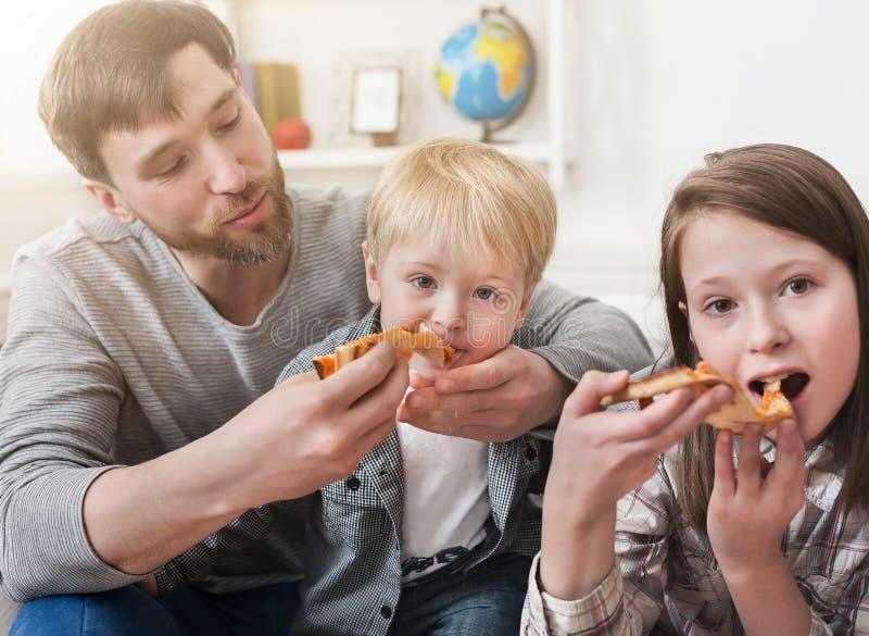 Portret van gelukkige familie die pizza thuis eten royalty-vrije stock afbeelding