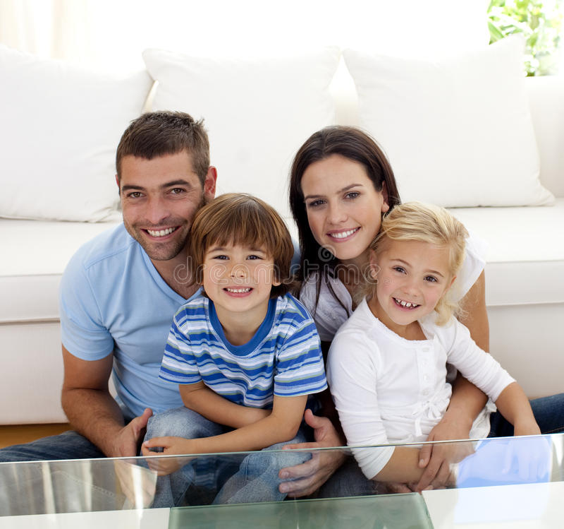 Portret van gelukkige familie die in woonkamer glimlacht royalty-vrije stock foto's