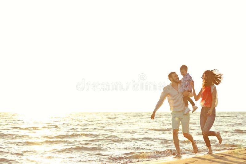 Portret van gelukkige familie en baby die van zonsondergang in de de zomervrije tijd genieten stock afbeelding