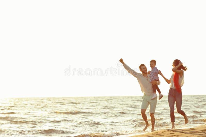 Portret van gelukkige familie en baby die van zonsondergang in de de zomervrije tijd genieten royalty-vrije stock foto's