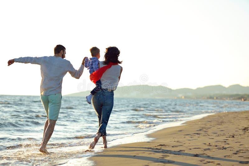 Portret van gelukkige familie en baby die van zonsondergang in de de zomervrije tijd genieten stock afbeeldingen