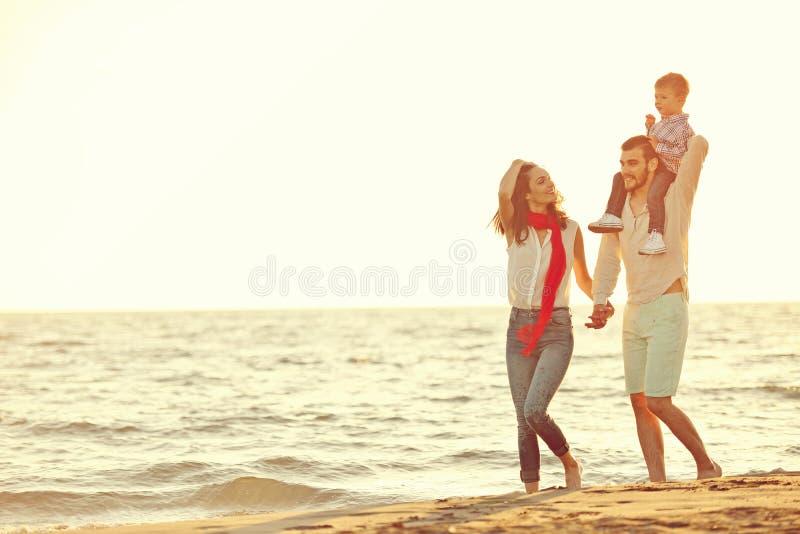 Portret van gelukkige familie en baby die van zonsondergang in de de zomervrije tijd genieten royalty-vrije stock afbeeldingen