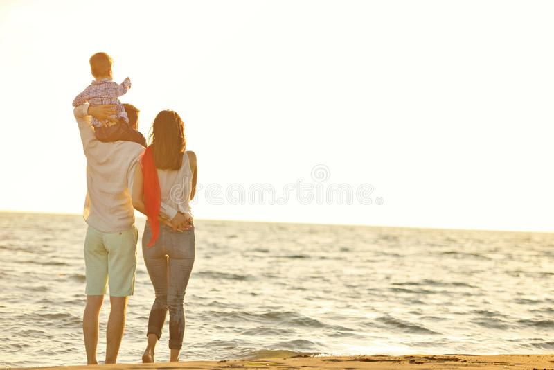 Portret van gelukkige familie en baby die van zonsondergang in de de zomervrije tijd genieten royalty-vrije stock foto