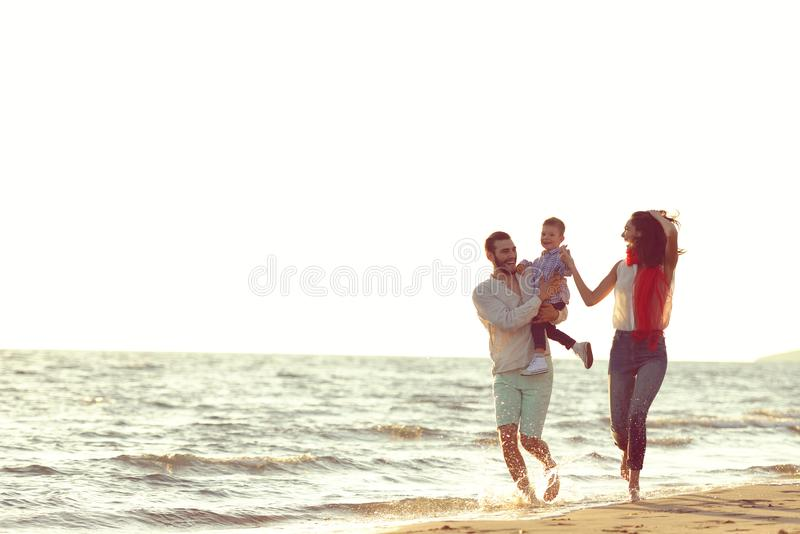 Portret van gelukkige familie en baby die van zonsondergang in de de zomervrije tijd genieten stock foto