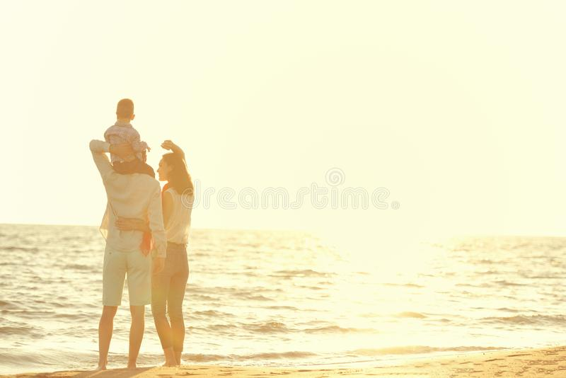 Portret van gelukkige familie en baby die van zonsondergang in de de zomervrije tijd genieten stock foto's