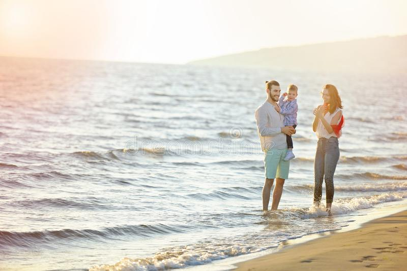 Portret van gelukkige familie en baby die van zonsondergang in de de zomervrije tijd genieten royalty-vrije stock afbeelding