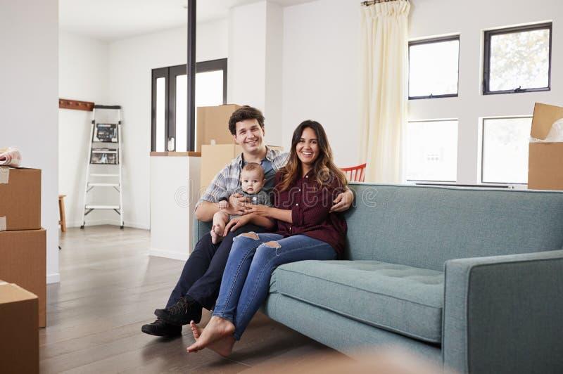 Portret van Gelukkige Familie met Baby die op het Nieuwe Huis van Sofa Surrounded By Boxes In bij het Bewegen van Dag rusten stock foto